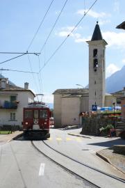 ABe 4/4 47 zieht einen Bernina Express durchs Nadelöhr bei der Kirche von S. Antonio