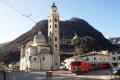 """ABe 4/4 55 und 52 überqueren den Platz vor der Kirche """"Madonna di Tirano""""."""