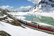 ABe 4/4 III 56 und 54 (verschandelt) ziehen einen Bernina-Express dem Lago Bionco entlang. Hinten ist die südliche Staumauer zu sehen.