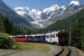 Die RhB-Werbetriebwagen ABe 4/4 51 und 52 vor einem Bernina Express in der Montebello-Kurve oberhalb Morteratsch