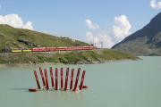 """ABe 4/4 44 und 48 mit Zug 1645 kurz vor Ospizio Bernina. Im Lago Bianco schwimmt die Installation """"Ark Sound"""" von Daniele Ligari."""