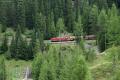 Ge 6/6 II 704 mit einem langen Güterzug oberhalb des Zuondra-Kehrtunnels