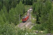 Ge 6/6 II 704 verlässt mit einem langen Güterzug den Zuondra-Kehrtunnel