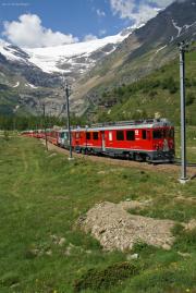 ABe 4/4 III 54 (es geht doch auch ohne Werbung!) mit einem BEX zwischen Alp Grüm und Drachenloch. Im Hintergrund der Palügletscher