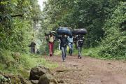 Träger bringen Gepäck von Touristen runter zum Gate. Marangu-Route, Tag1